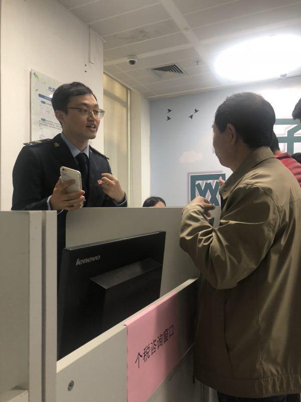 工作人员持手机向咨询者展示个税APP 每日经济新闻记者 潘婷 摄